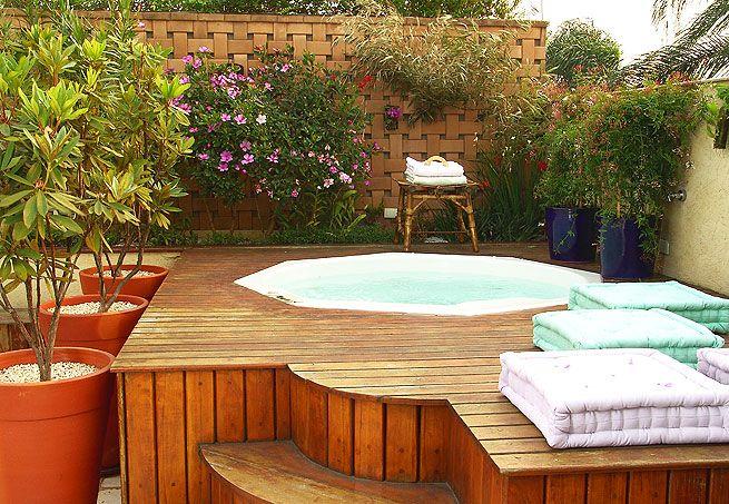 Deque com spa no jardim de uma cobertura. A hidromassagem tem capacidade para oito pessoas. Futons, vasos com plantas e flores dão mais charme ao ambiente