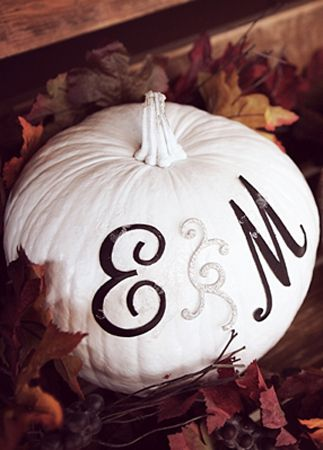 Pumpkin wedding decorations for a fall wedding. White painted pumpkin with the bride and groom's initials