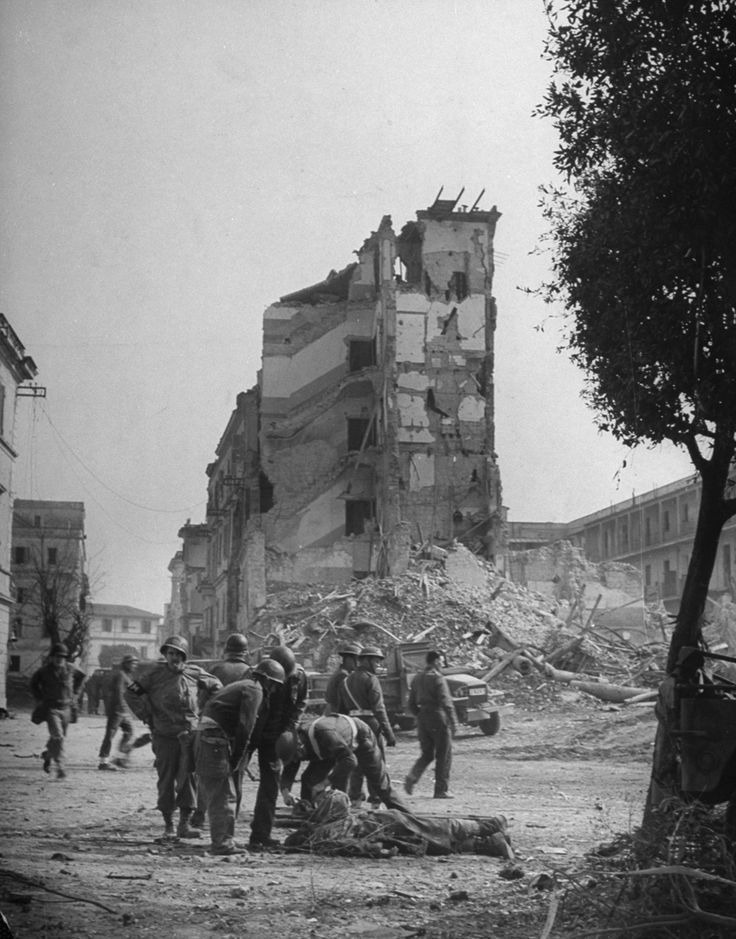 """The Allies at Anzio: Rare Photos From WWII's Italian Campaign   LIFE.com. Caption from LIFE. """"In ruined Anzio American and British soldiers gather around man who has just been hit by fragments of a shell bursting in the street. Casualty had come ashore from the harbor 40 seconds before."""""""
