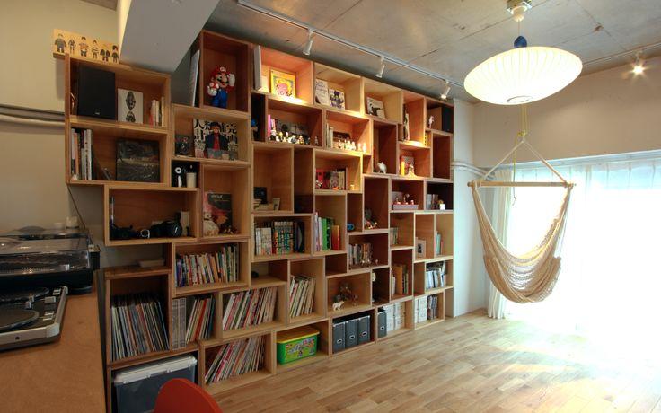 """築30年のマンションをリノベーションして誕生した広々リビング。39個のボックスをランダムに組み合わせて、壁一面に広がる""""本棚""""を作りました。"""