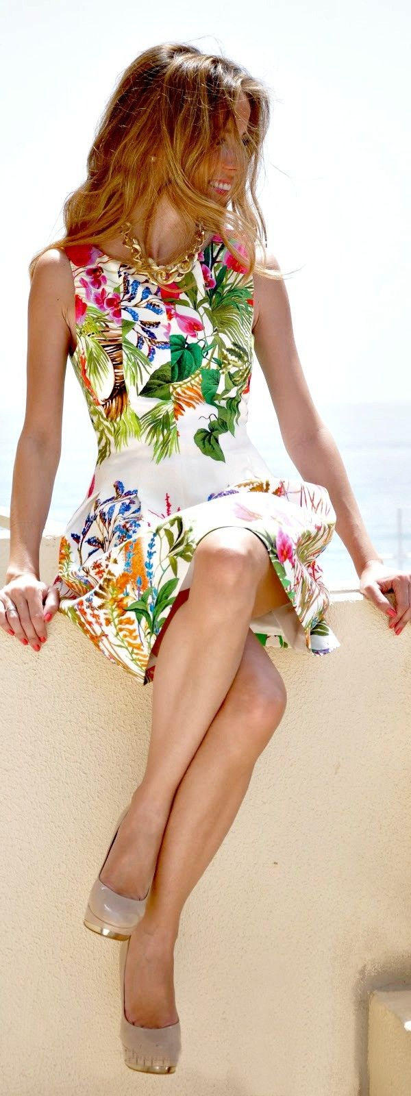 Corally smiling lightly tanned strawblonde in sleeveless white floral skater dress, gold soled nude stiletto platforms