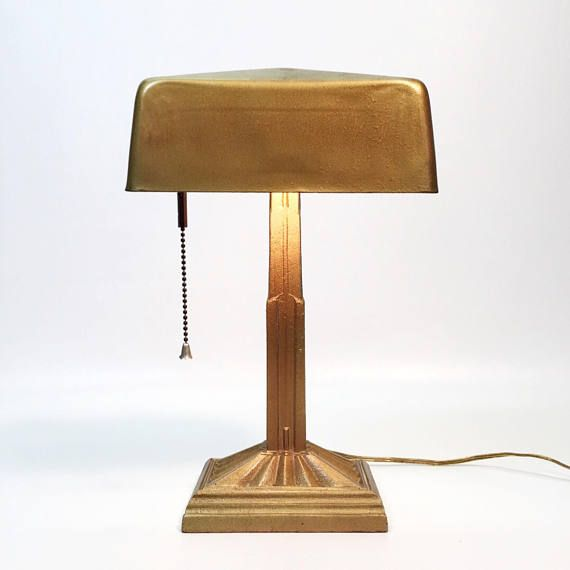 Art Deco Golden Bank Tellers Desk Lamp, Industrial Lamp, Drafting Lamp, Gooseneck Desk Lamp, Antique Piano Light, Skyscraper Tower Lamp  This desk lamp is a beautiful example of the craftsmanship, its base is a solid cast metal, grooves for pens and office supplies. The golden metal lamp shade swivels and turns and fits a standard bulb. Bulb not included. Cast metal painted gold. Small circle possibly a sticker marking on the shade. Adjustable and swivelling shade.  Measures Approx 6lbs…