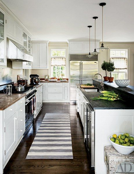 A trio of pendant lights from Laurin Copen Antiques hangs in the kitchen, which is outfitted with a Sub-Zero refrigerator and wine cooler, a Viking range and hood, and a Madeline Weinrib rug