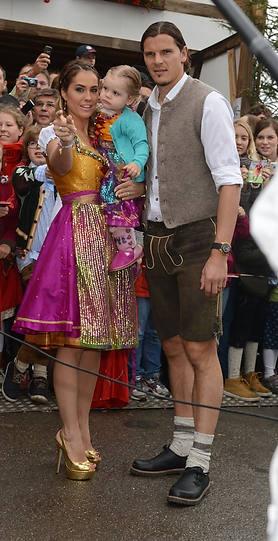 Er trägt Haferlschuhe, sie goldene Stilettos: Daniel van Buyten, seine Frau Celine und Töchterchen
