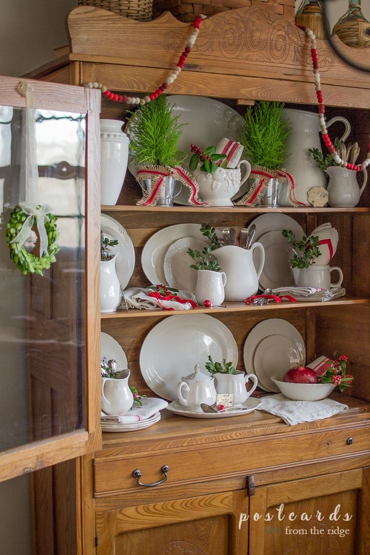 So many pretty items in this farmhouse styled antique hutch. Love the ironstone and vintage silver.