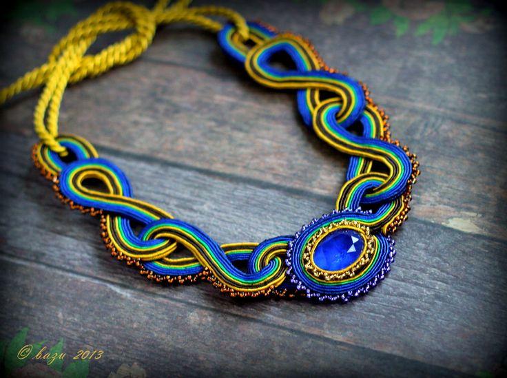 Pávie pero II. Ručne šitý autorský náhrdelník vo farbách pávieho perá.  Modrý sklenený kabošón je obšitý zlatožltým a fialovým Toho rokajlom, sutaškami (zelená, modrá, žltá, hnedá) a po vonkajších okrajoch aj hnedým Toho rokajlom.  Náhrdelník sa viaže okolo krku zlatožltou šnúrou. Veľkosť: výška cca 15,5 cm (merané v kľude), šnúry na zaviazanie cca ...