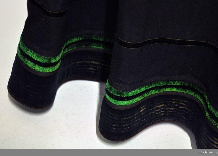 Stakk med med påsydd liv. Skjørtet er av svart ull i lerretsbinding, rynket øverst og med åpning/splitt foran. Nederst er det pyntebånd i svart og grønn fløyel, samt svarte ullbånd. Skoningen er 13 cm.Livet er av rød silkefløyel med kanting i burgunderrød vadmel. Baksiden er det påsydde rutete kantebånd. Hver skulderreim er brettet og sydd for hånd for å gjøre den kortere. Foran er det innfelt et annet ulltøy. Noen små hull på skjørtet.