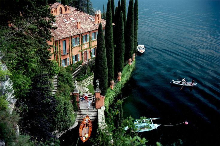 Giacorno and Stefania Montegazza welcome guests arriving by boat at their villa, La Casinella, on Lake Como, 1983.