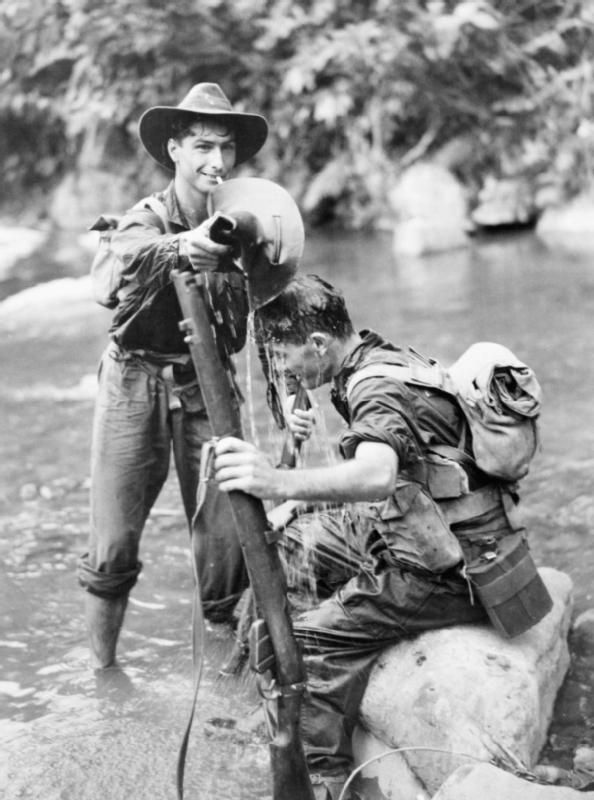 Two Australian soldiers cool off in a stream after a patrol in the Wonginara area of New Guinea (in the Torricelli mountains inland from Dagua). Signalman H Hobson pours a hatful of water over Private L Thwaites of 2/3 Australian Infantry Battalion. While the Americans were liberating the Philippines, the Australians faced thousands of Japanese holding out in New Guinea, the Solomons and New Britain.