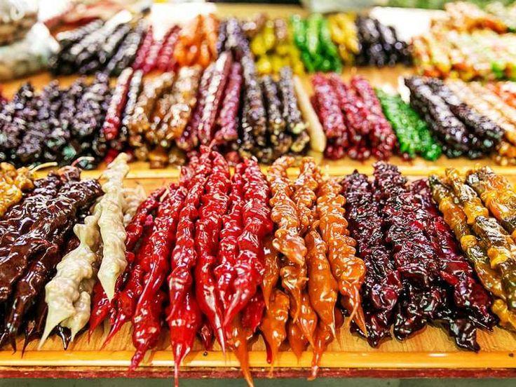 غذاهای گرجستان  Georgian food  Churchkhela (Georgian: ჩურჩხელა, Georgian pronunciation: [tʃʰurtʃʰxɛlɑ]) is a traditional Georgian[1][2][3] candle-shaped candy. The main ingredients are grape must, nuts and flour. Almonds, walnuts, hazel nuts and sometimes raisins are threaded onto a string, dipped in thickened grape juice or fruit juices and dried in the shape of a sausage.
