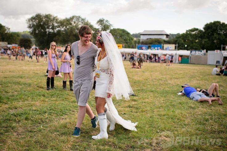 英南西部サマセット(Somerset)州ピルトン(Pilton)で開幕した世界最大級の野外音楽祭典「グラストンベリー・フェスティバル(Glastonbury Festival)」の会場を歩く、結婚式を挙げた直後のカップル(2014年6月25日撮影)。(c)AFP/LEON NEAL ▼27Jun2014AFP|世界最大の英野外音楽祭「グラストンベリー」が開幕 http://www.afpbb.com/articles/-/3018900 #Glastonbury_Festival