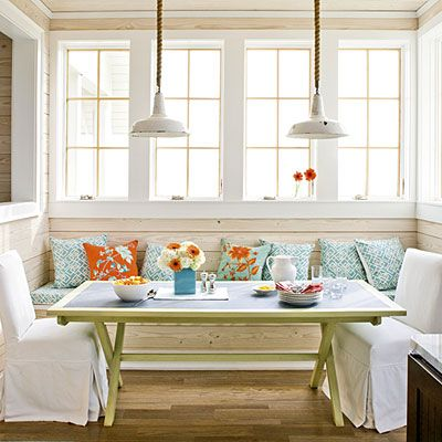 Utilize Corner Spaces | A window-filled alcove in this beach house functions like a dining room with a casual table, two slipcovered end chairs, and a pillow-topped banquette. The built-in bench and wall of windows make this small space seem much larger. Two vintage light fixtures hung with nautical rope instead of standard chains illuminate the space.
