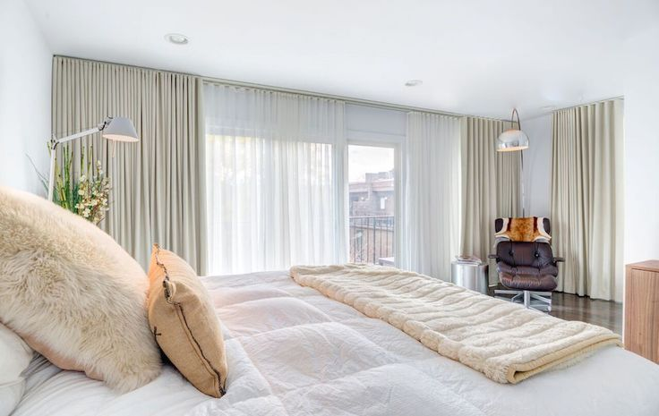 Whites, Beiges, and Neutrals meld perfectly in this bedroom. Sheers and eggshell-colored blackout drapes come together on a double track system to create a fabric wall.