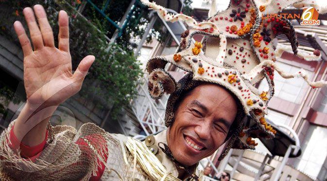 Menggunaka busana mirip seorang Ksatria yang didominasi oleh Warna   merah dan kuning emas ditambah dengan mahkota setinggi 0,5 meter di   kepalanya, Jokowi tak hentinya melambaikan tangan.(Liputan6.com/Faisal   R Syam) http://lp6.co/1AcI