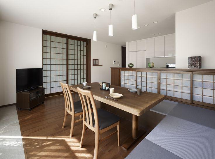 【#ミサワホームイングデザインリフォーム 】 収納充実の和モダンなリビングキッチンにリフォーム。隣の和室との出入口だけでなく、キッチンとの目隠しを兼ねた腰高のカウンター収納にも、柔らかな和紙調のガラスをはめ込んだ格子引き戸を採用。 L型のベンチ収納は、座面に藤鼠色のカラー畳を貼りました。庭側の床には、大版のタイルを敷いてアクセントに。 #リフォーム #リノベーション #住まい #インテリア #インテリアデザイン #インテリアコーディネート #リビングインテリア #リビングキッチン #ダイニング #カラー畳 #収納 #格子 #引き戸 #和モダン #ベンチ #ミサワホームイング #intelimia