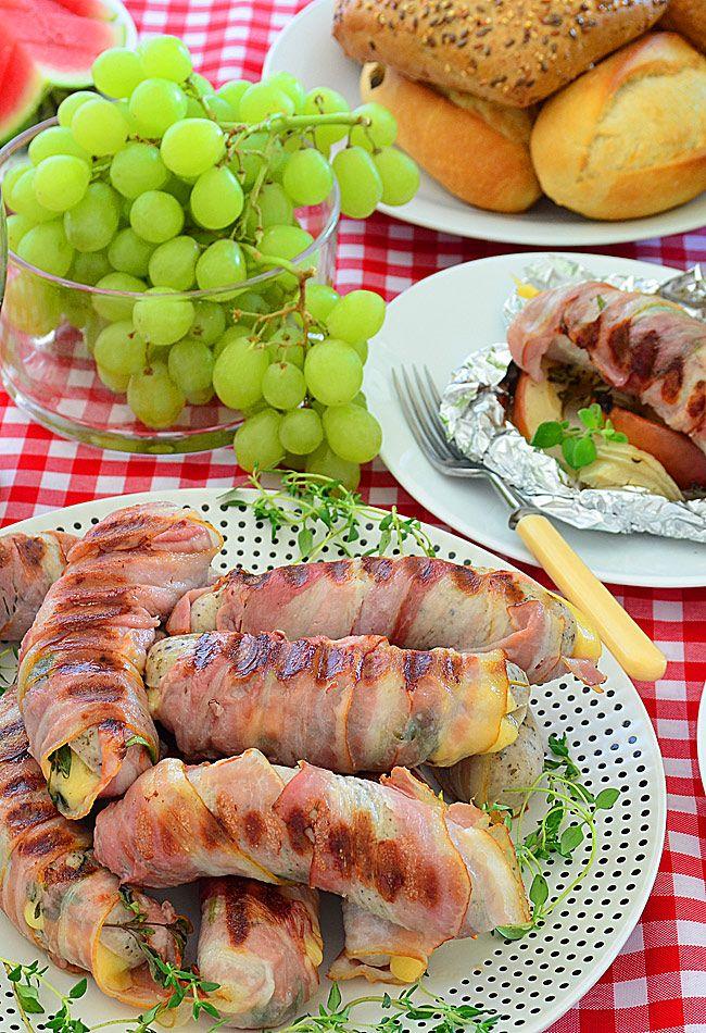Biała kiełbasa z grilla - nadziewana serem, zawinięta w boczek podana z prażoną cebulą i jabłkiem - MniamMniam.pl