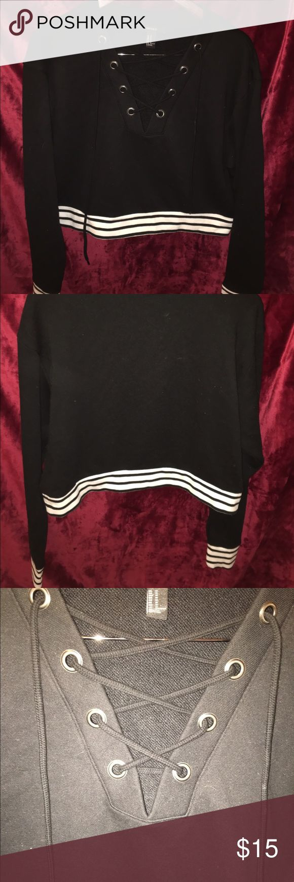 Black laced up crop crewneck crop top sweatshirt Women's size medium. This black crop top crewneck is new without tags! It features a black and white striped sleeve trim and bottom trim, it is cropped, and it has a black lace up laced up front! Don't miss out on this great deal!    Crewneck, crew, hoodie, sweatshirt, Kylie Jenner, Kylie, hooded, black, white, lace up, laced up, tied up, ties, tie up, Tops Sweatshirts & Hoodies