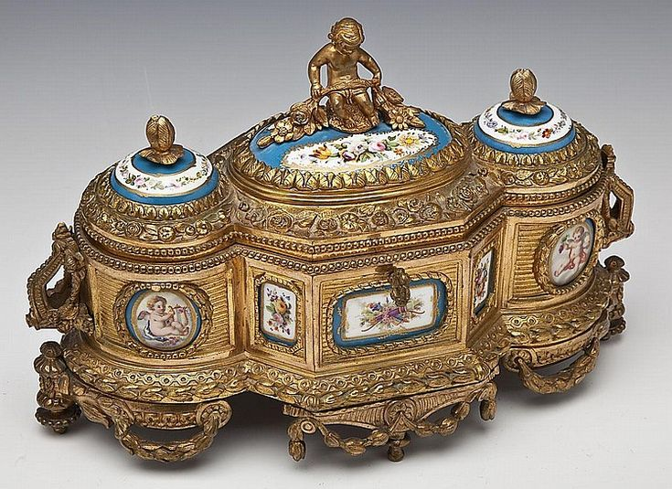 "DESCRIPTION: A French Sevres style dore bronze casket with lock by Tahan decorated overall with flowers and laurel swags and inset with ten porcelain panels handpainted with flowers, putti and crossed torch and quiver. Lid with three handpainted convex porcelain panels, side handles and central figural putti finial. Interior lined with maroon velvet and braid trim with central compartment flanked by two glass inkwells with gilt and silvered metal screw-on caps. Marked to the lockplate ""Tahan…"