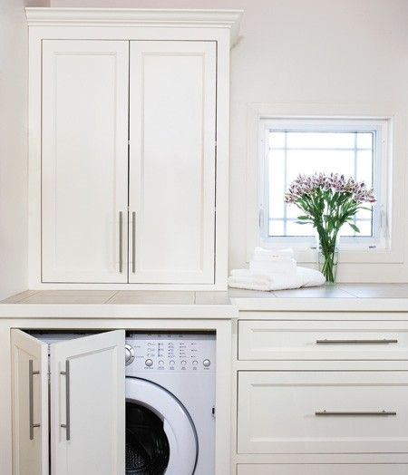 Hidden Design Idea  Clever cabinetry conceals laundry appliances in this classic laundry room.    A bi-fold door conceals a front loading washer/dryer in this light-filled laundry room. Shaker-style cabinets provide plenty of storage for laundry essentials and keep the space clutter-free.        Photographer: Janet Kimber