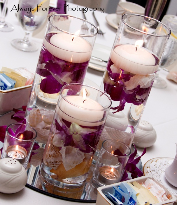 Cylinders with floating orchids and candles with shells in the base to pull a beach theme on to the tables