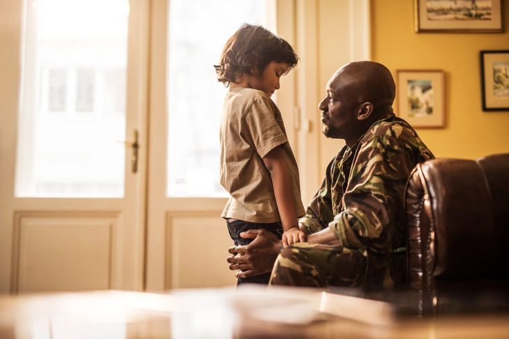 Sad African American boy talking to his military dad who is leaving to war.