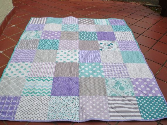 This colorful patchwork quilt measuring 36 by 48 in grey, teal and lavender featuring chevrons, quatrefoil, stripes and polka dots would be perfect as a lap quilt or as a baby quilt for either a girl or a boy; newborn, infant or toddler.(FYI: crib mattress is 27 by 52)  As a traditional 3 layered quilt: The quilt top, made of 100% quality designer cotton fabrics including Riley Blake, is machine pieced. A layer of cotton batting in the middle adds warmth to the quilt. Made with an ultra-soft…