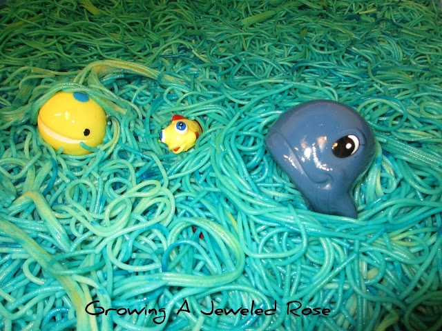 cooked spaghetti sensory pool - see page for instrux, and also: (two large packs of cooked noodles (the Dollar Tree), then ran them under cold water, added a bit of vegetable oil to prevent sticking, then colored the noodles using food coloring)