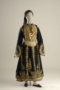 This bridal and festival costume from Argyrokastro, with minor variations in the headdress, was worn by both Greek and Turkish women alike. It consists of a long white chemise, short waistcoat, long black overcoat embroidered in gold, and a gold belt and buckle. The breast is covered by the armatha, a chain ornament with gold-plated coins, which was worn for the wedding and then became a family heirloom. The head is covered with a silk headscarf hemmed with gold embroidery.