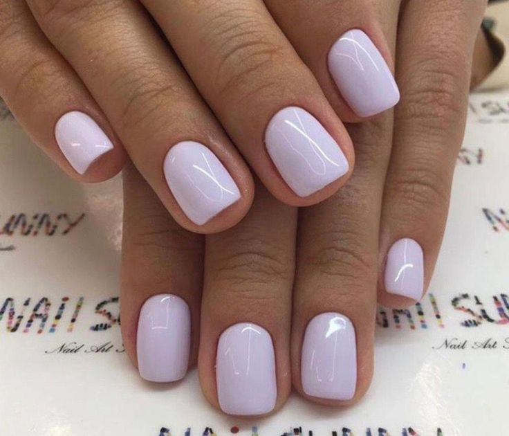 Short, natural square nails covered in a decadent, opaque lavender nail polish. …