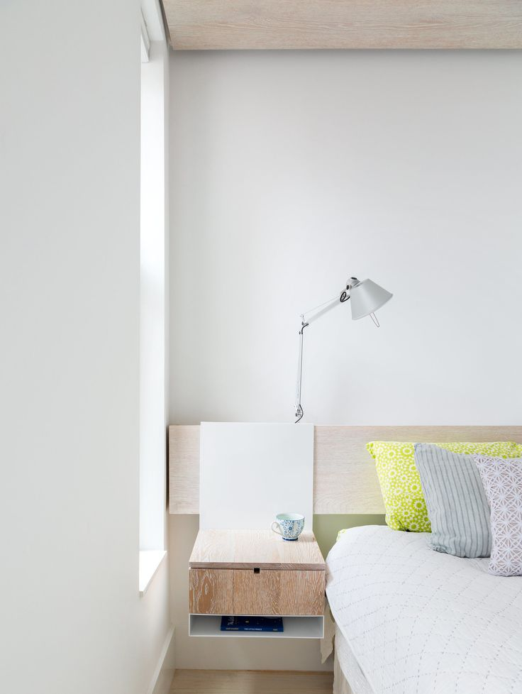 Rather than clutter the master bedroom with furniture, Frame Design Lab created a system where night stands hang from a wall-mounted headboard.