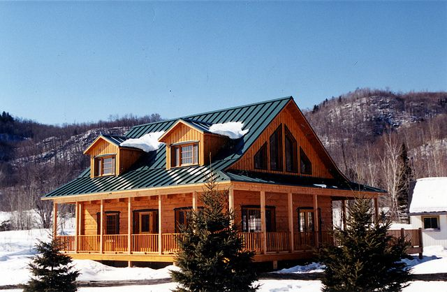 Log Home With Green Tin Roof And Wrap Around Porch