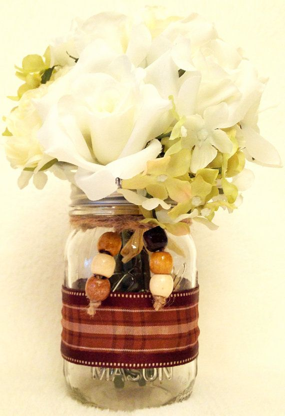 Mason Jar Country Decor Brown Plaid Ribbon  Beads by KimsMasonJars.  Ball mason jar with brown plaid ribbon around the middle of jar. Jute is wrapped the neck of the jar and holds a total of 6 small, round, wooden beads to help give this mason jar its country flair.  Use this jar to hold flowers or add a LED tea light to cast a subtle glow. Or, spice up your desk by adding pencils and pens.  https://www.etsy.com/shop/KimsMasonJars