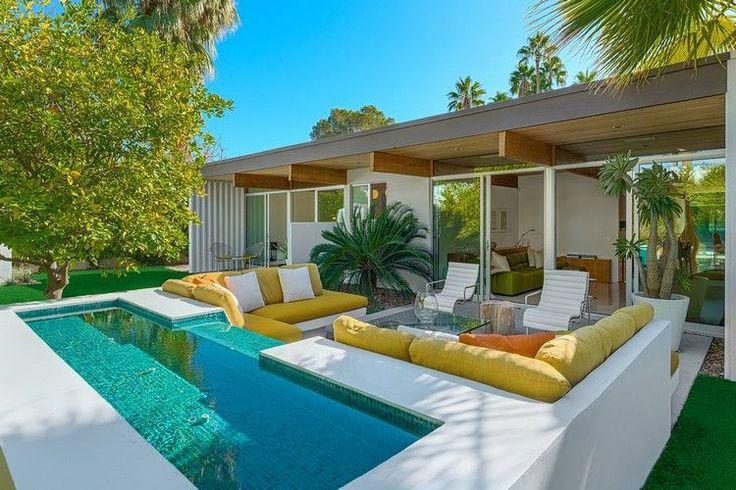 Aménagement jardin moderne avec piscine extérieure et canapé d'angle décoré de galettes de siège jaunes
