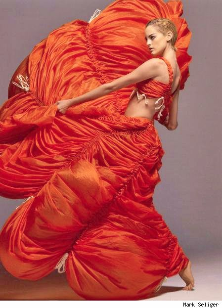 "Nylon parachute dress in International Orange, 1974. Kamali began experimenting with unusual materials, producing dresses and jumpsuits from parachute silks. To capitalize on the original use of the fabric these pieces were constructed with drawstrings in place in order to adjust the fit of the garment. Her 1975 ""parachute"" collection was a huge success. In later years, the material used would be changed to a more durable and water-repellent nylon."