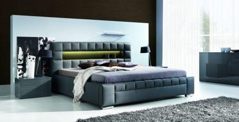 Łóżko Cezar o tapicerowane eko skórę, obok stoliczek nocny.