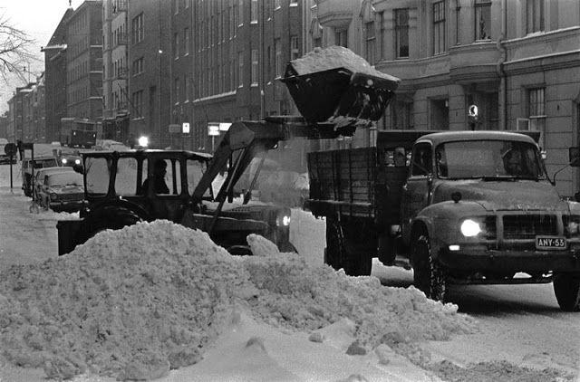 Traktori nostamassa lunta kuorma-auton lavalle talvipäivän hämärässä lumisella Mariankadulla. 1969