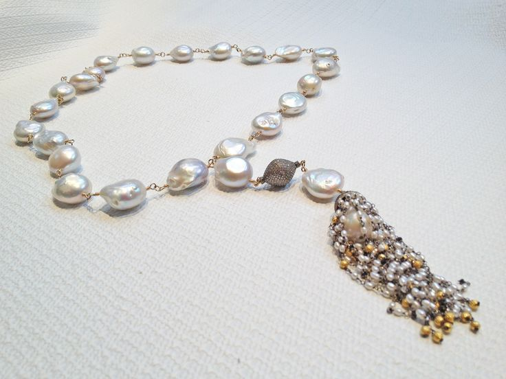 This #pearl #necklace is a great example of how mixing different materials can make your designs really pop! Large, white baroque freshwater pearls #wirewrapped on #14K #gold wire to go around the neck. Tiny rice #pearls, black #diamond roundel beads, and 18k gold Bali #beads making up the cap and tassel. #baroquepearls #freshwaterpearls #handmadejewelry #wirewrapping #beadedtassel