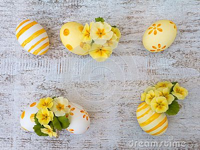 White and yellow easter eggs decorated by stripes, dots and flowers and primrose on the white wooden board