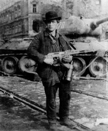 One of the very brave Hungarian rebel posing with his AK-47 in front of a Soviet tank in 1956.Soviet killing and raping and raid Hungarian nation !!!