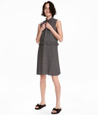 Mørkeblå. Kort kjole i vævet viskose med trykt mønster. Kjolen har kort flæsekrave med smal elastik og V-udskæring med bindebånd foroven. Skåret i taljen