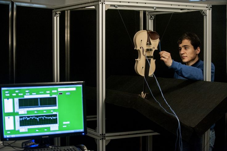 """Dr. Alessandro Liberatore """"hammering"""" the violin to analyse its vibrational properties"""