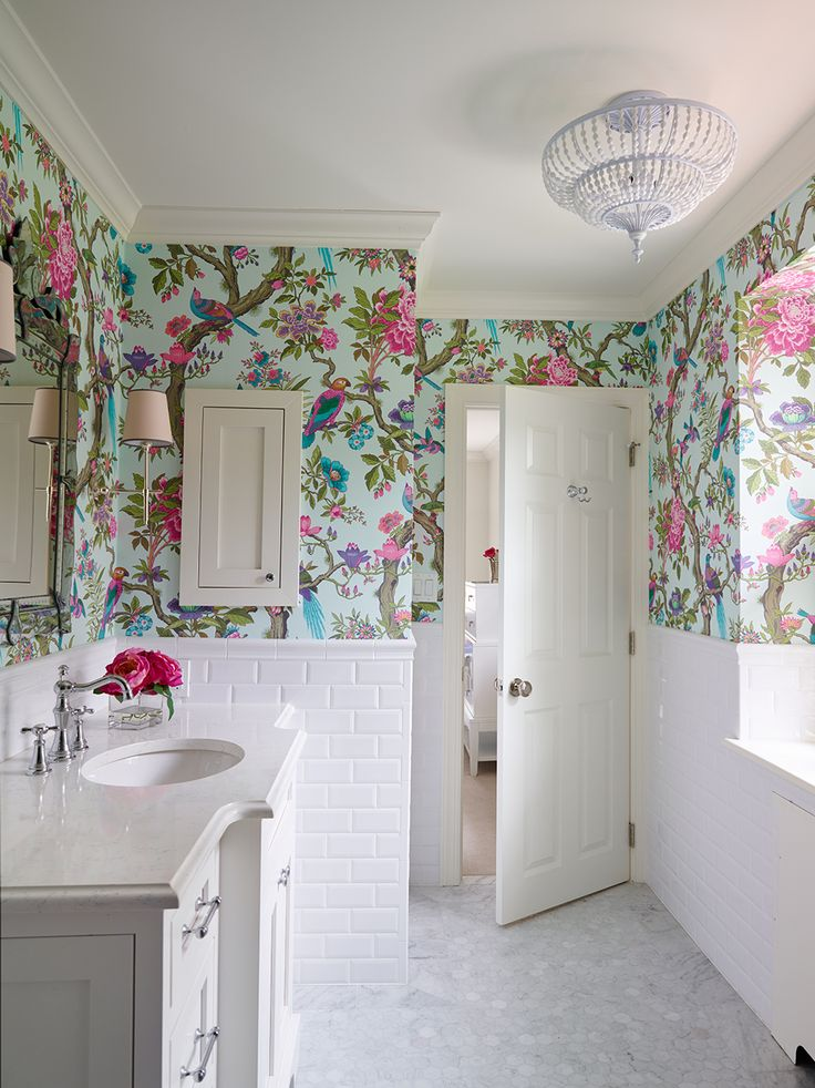 Bold Feminine Little Girls ensuite Bathroom featuring this Floral wallpaper by Cole and Son. Interior design by SHOPHOUSE. White subway tile walls and hexagon marble floor. Venetian Mirror and Bryant Sconce, Feiss chandelier. Girls bathroom with pink and purple wallpaper. www.shophousedesign.com