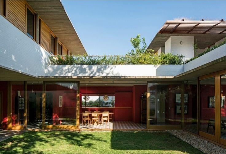 Casa na Lapa - Brasil Arquitetura. A marquise de concreto marca a residência, em São Paulo, que avança sobre o terreno em aclive. No térreo, além das amplas portas de vidro que se abrem ao jardim, chama a atenção a parede vermelha que marca a transição entre os ambientes