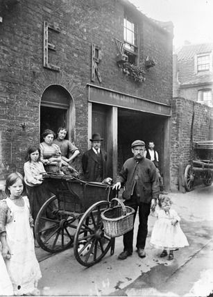 """The cat's meat man pushed his barrow around East End streets selling cheap meat to families as pet food… The decoration on the house marks the coronation of Edward VII."" This photo was taken circa 1902 by John Galt, a missionary from the London City Mission, and was used to illustrate lantern slide lectures which were given to raise funds for the work of the mission. Another missionary is standing in the centre with the family."