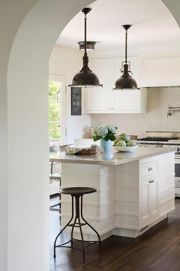 Interesting trim detail on the island, gorgeous lights and stool, and check out that herringbone backsplash!