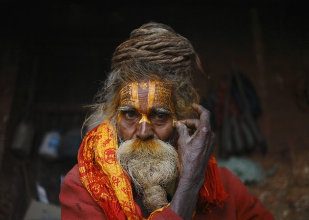 A Hindu holy man, or sadhu, applies paint on his forehead ...
