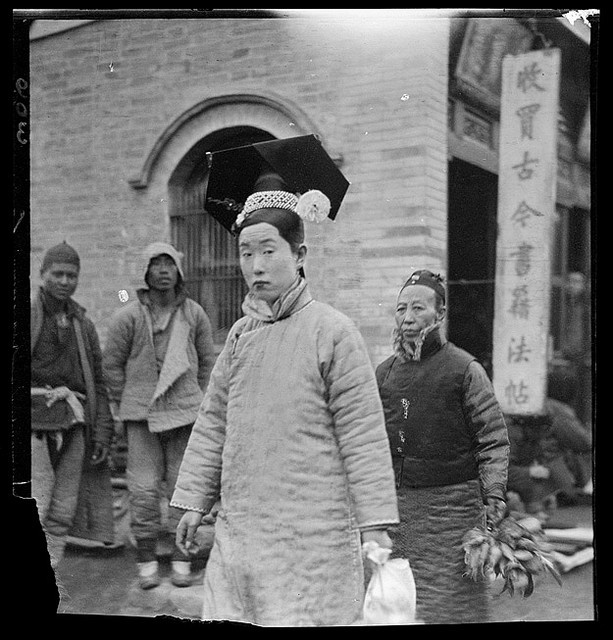 1912, Manchu woman in foreground -- see men in the background, dressed in Han clothing