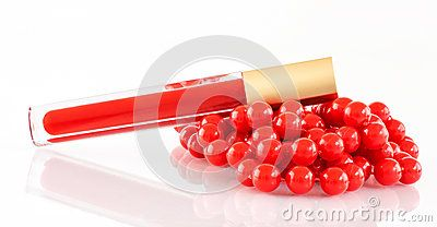 A closeup of vivid  red lipgloss and a red bead necklace