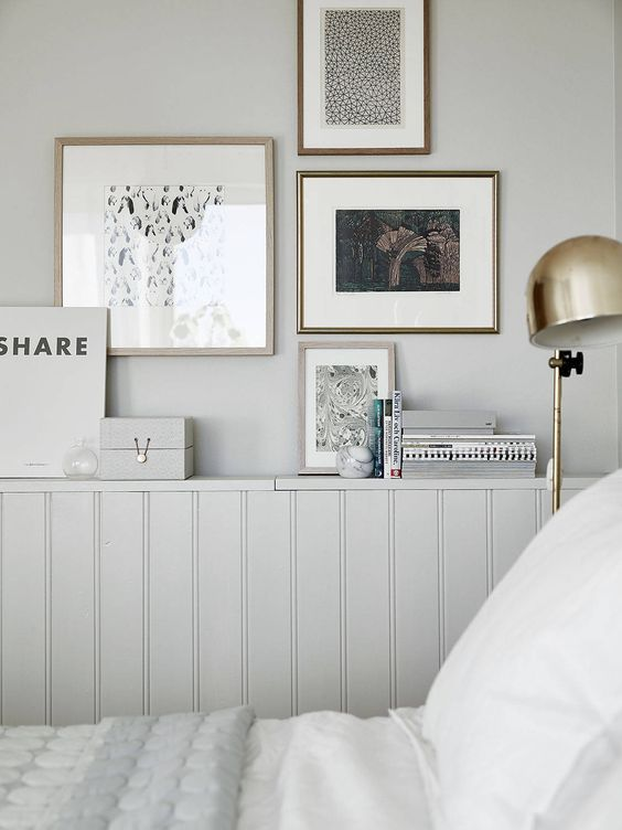 Pale grey panelled bedroom with gallery wall