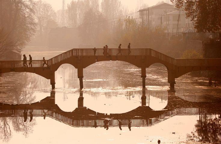 Srinagar, India   People walk on a wooden footbridge across a canal during an autumn day  Photograph: Danish Ismail/Reuters